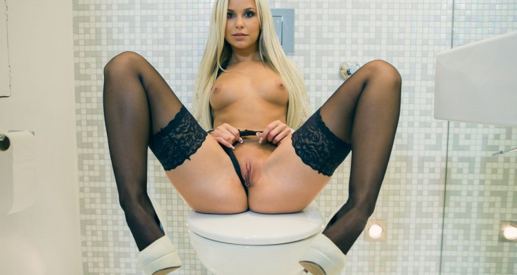 Lara with her legs spread in the bathroom